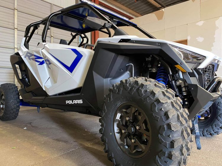 a black and white rzr with big wheels sitting in a garage